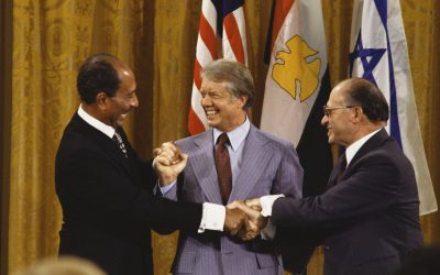 Jimmy Carter et al. standing next to a man in a suit and tie