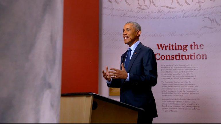 Barack Obama holding a sign
