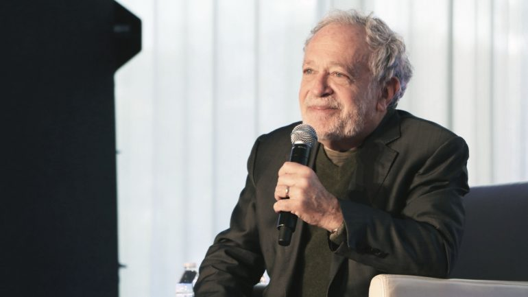 Robert Reich wearing a suit and tie talking on a cell phone