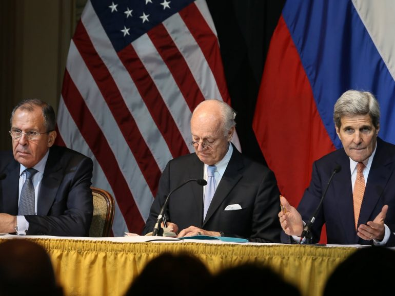 Sergey Lavrov, John Kerry sitting in front of a curtain