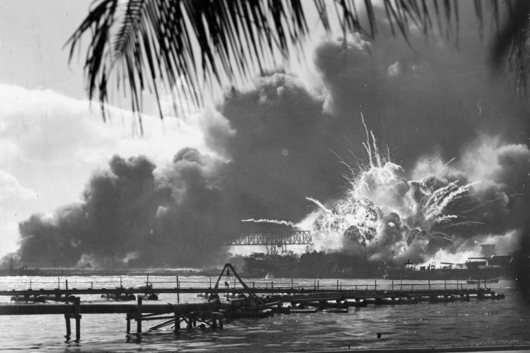 Smoke coming out of the water with Pearl Harbor in the background