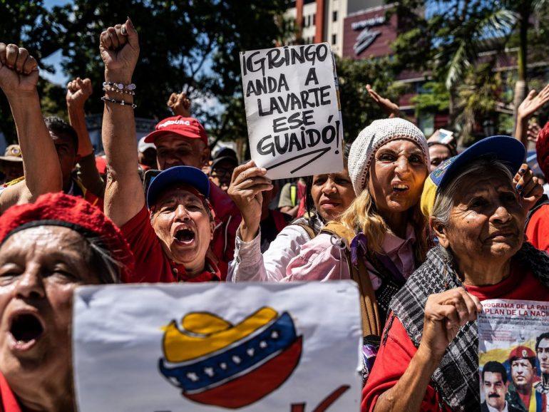 Nicolas Maduro, Hugo Chavez holding a sign