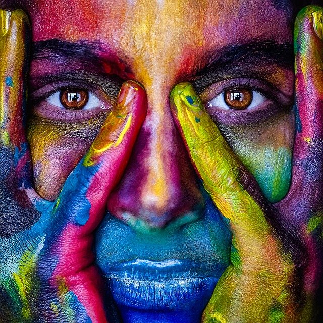A person wearing a colorful face